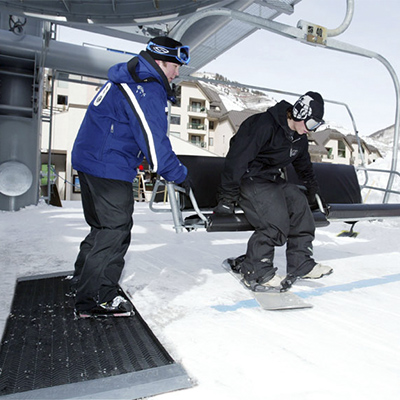 Portable heated traction mat being used at ski lift.